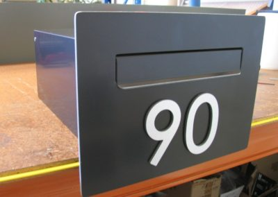 Satin Black Cave Letterbox shown on bench before packaging
